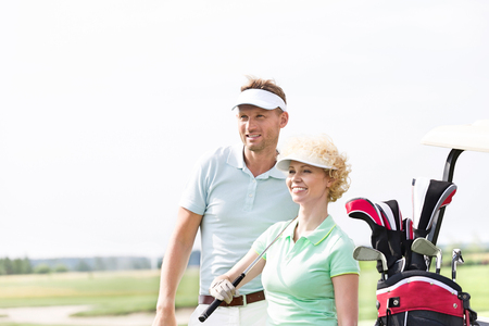 Smiling golfers standing at golf course against clear sky Stock Photo