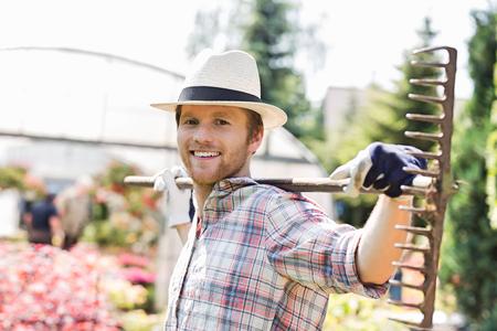 Portrait of smiling gardener carrying rake on shoulders at plant nursery Imagens