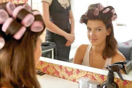 Portrait of young woman with hair curlers smiling