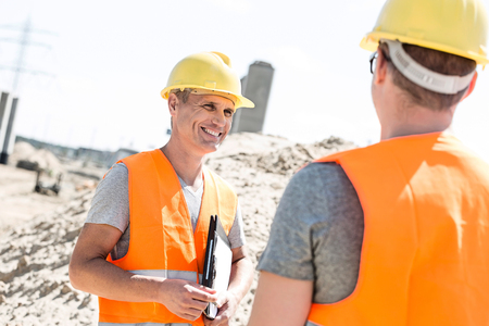 Happy supervisor discussing with colleague at construction site Stok Fotoğraf