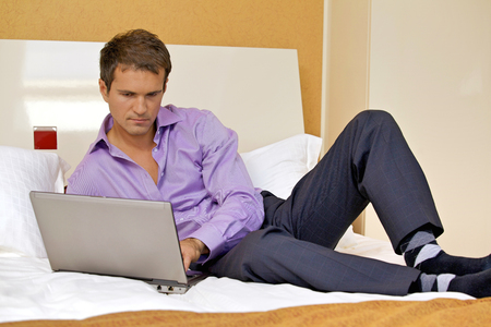Young man using laptop on bed