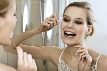 hygeine: A young woman flossing her teeth