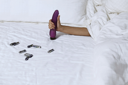Womans hand holding dildo in bed