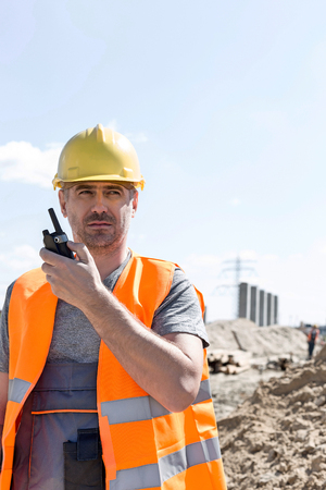 Confident supervisor using walkie-talkie at construction site against sky