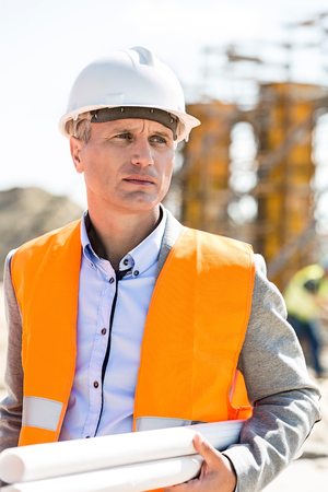 Thoughtful architect looking away while holding blueprints at construction site