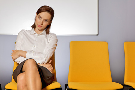 legs crossed at knee: Portrait of businesswoman sitting in waiting room