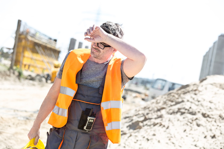 Tired construction worker wiping forehead at site Фото со стока