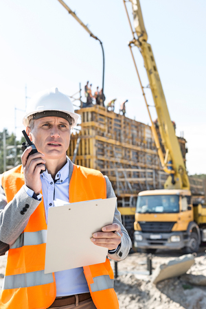 Male supervisor using walkie-talkie while holding clipboard at construction site Stock Photo