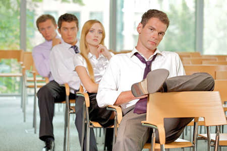 four people: Business executives sitting in row at office LANG_EVOIMAGES
