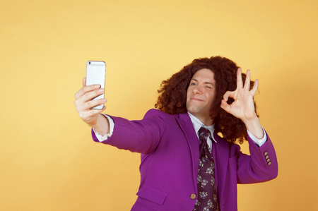 Caucasian man with afro wearing Purple Suit taking a selfie Imagens