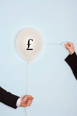 Cropped hands holding needle and popping balloon with pound symbol