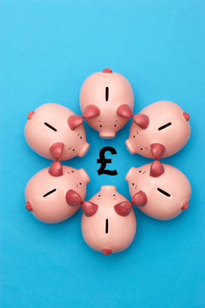 Piggy banks on blue background surrounding a GBP Symbol