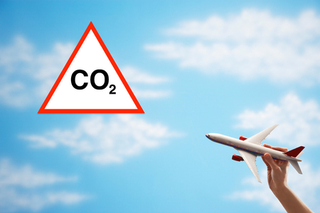Closeup of womans hand flying toy plane against cloudy sky with warning CO2 sign