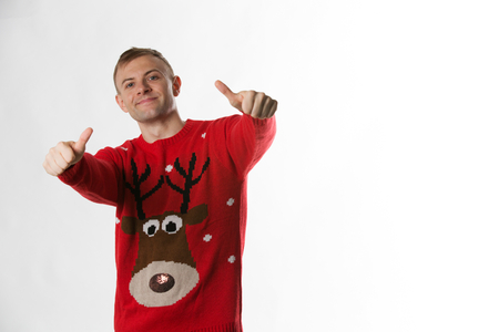 Caucasian man with hand on hips whilst wearing a christmas jumper looking to camera Stock Photo