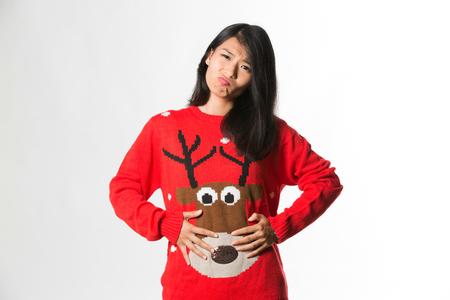 肖像画クリスマス sweatershowing の女性の彼女は灰色の背景にあまりにも多くの食品を食べています。