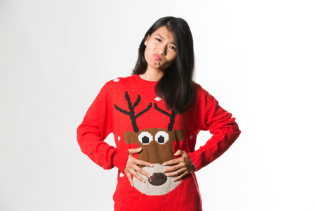 Portrait of woman in Christmas sweatershowing she has eaten too much food over gray background