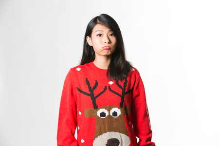 glum: Portrait of woman in Christmas sweater standing making funny face over gray background