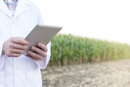 Midsection of mature scientist using digital tablet at farm 写真素材