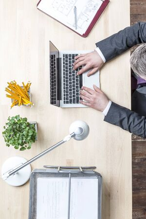 Directly above view of mature businessman using laptop at office
