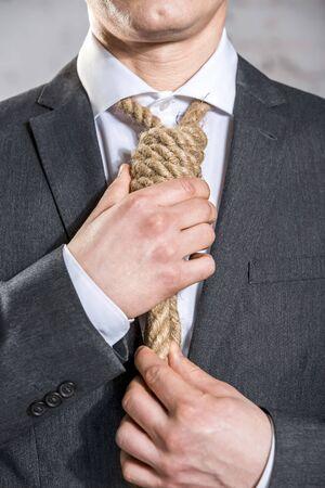 Midsection of businessman adjusting noose at office