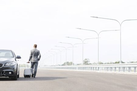 Businessman walking with suitcase by car on road against sky