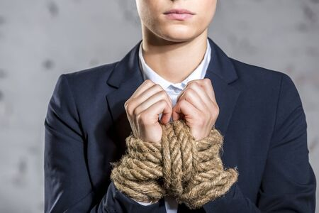 Midsection of young businesswoman standing with tied hands at office 写真素材