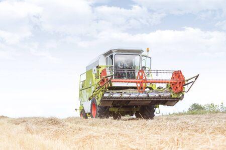 Farmer driving harvester on field at farm against sky