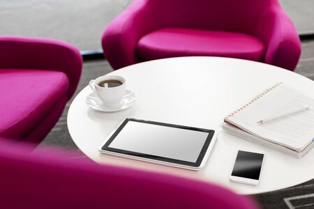 High angle view of digital tablet with coffee cup and smartphone on table by chairs at office 写真素材