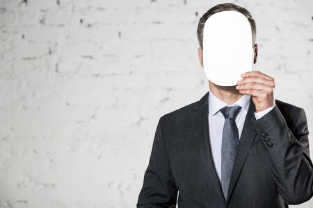 Mature businessman covering face with blank paper against white brick wall at office