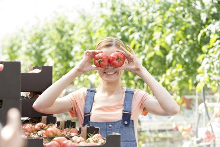 Smiling woman playing with tomatoes while standing in farm