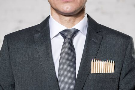 Midsection of businessman with colored pencils in pocket against wall