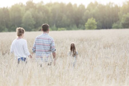 Rear view of family walking amidst crops at farm