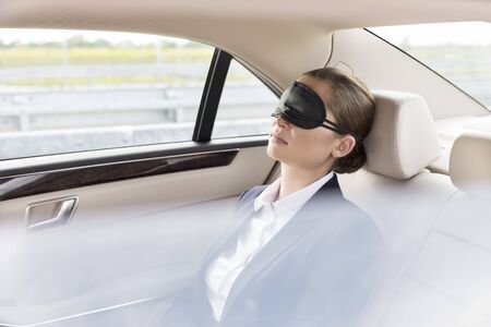 Businesswoman napping with mask in car during travel