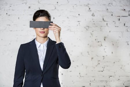 Young businesswoman covering eyes with paper against white brick wall at office 写真素材