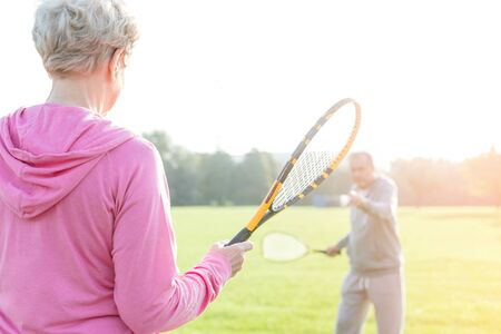 Senior woman holding tennis bat while playing with man in park 写真素材