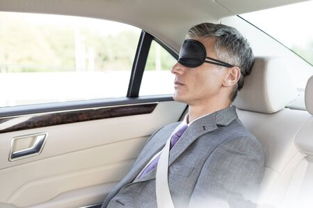 Mature businessman napping while wearing eye mask in car 写真素材