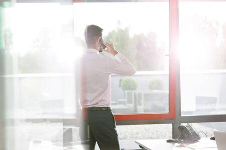 Businessman talking on smartphone by window at office desk 写真素材