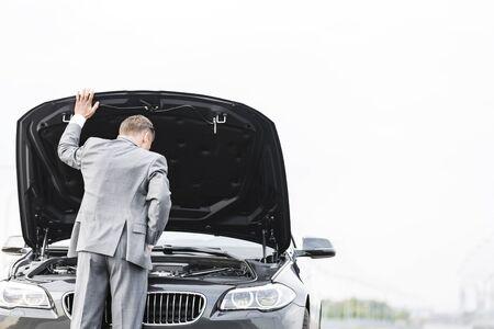 Businessman looking at breakdown car against sky 免版税图像