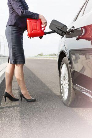 Unterer Abschnitt der Geschäftsfrau, die Auto mit Kanister auf der Straße tankt