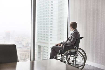 Thoughtful disabled businessman looking through window in boardroom at modern office Stock fotó
