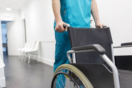 Midsection of nurse pushing wheelchair in hospital corridor Stok Fotoğraf