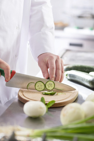 Midsection of mature chef cutting cucumber on board in restaurant kitchen 写真素材