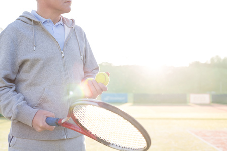 Midsection of mature man holding tennis balls and racket on court against clear sky 写真素材