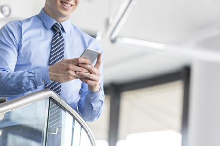 Midsection of smiling businessman using smartphone while standing at office