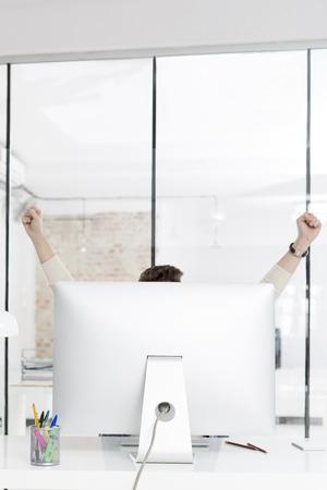 Businessman celebrating success while raising hands at computer desk 写真素材