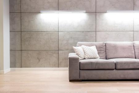 Empty sofa against illuminated wall in apartment