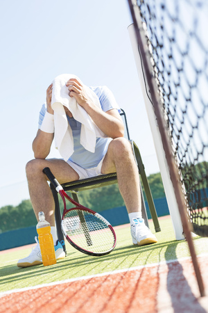 Full length of exhausted mature man with head in towel sitting on chair by net at tennis court on sunny day 写真素材