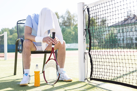 Full length of tired mature man with covered head sitting on chair by net at tennis court on sunny day