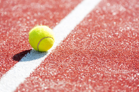 High angle view of tennis ball on red court during sunny day