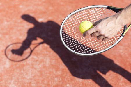Cropped hand of mature man serving tennis ball on red court during sunny day 写真素材